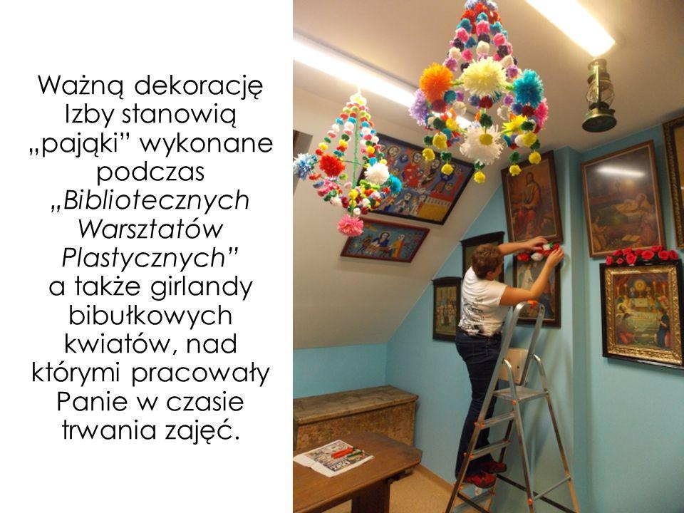 """Ważną dekorację Izby stanowią """"pająki"""" wykonane podczas """"Bibliotecznych Warsztatów Plastycznych"""" a także girlandy bibułkowych kwiatów, nad którymi pra"""