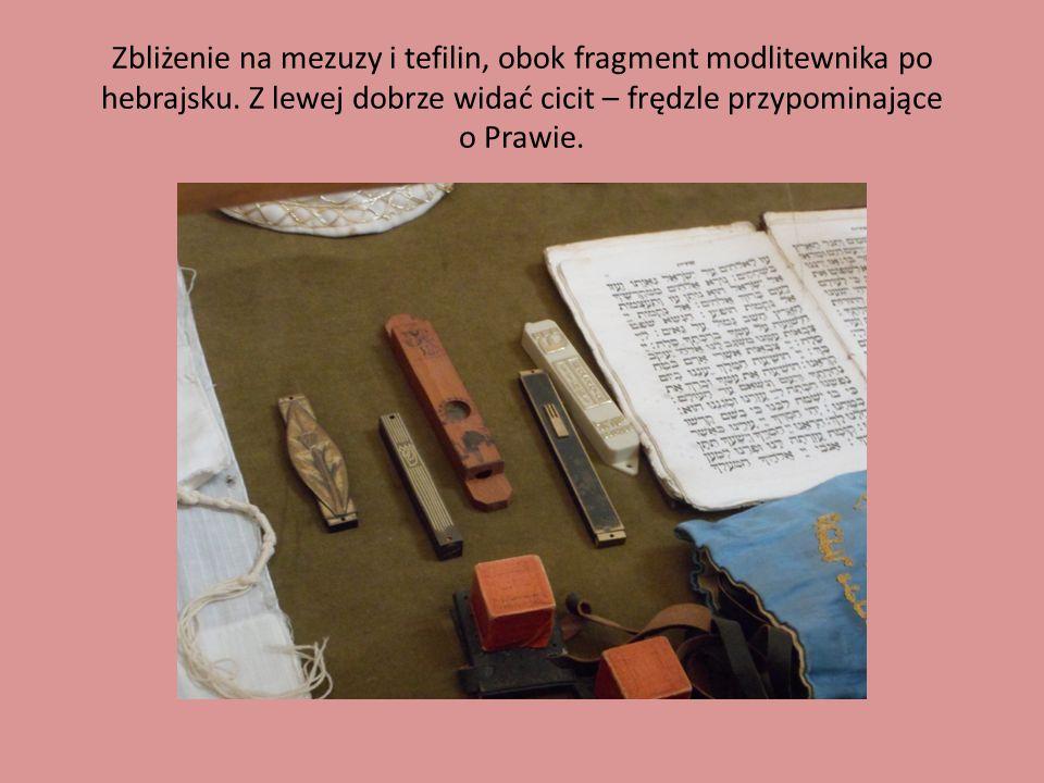 Zbliżenie na mezuzy i tefilin, obok fragment modlitewnika po hebrajsku. Z lewej dobrze widać cicit – frędzle przypominające o Prawie.