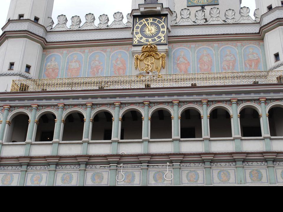 Ściana frontowa zdobiona jest szesnastowiecznym, trójkondygnacyjnym loggie, a między łukami znaleźć możemy połączone w pary kobiece alegorie cnoty: Mi