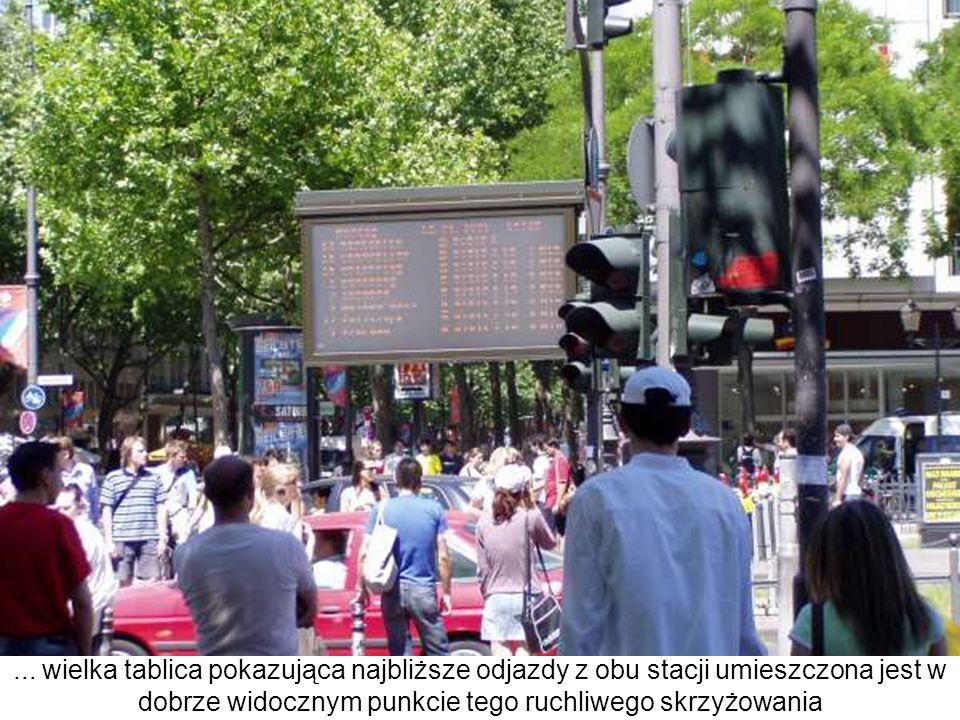 ... wielka tablica pokazująca najbliższe odjazdy z obu stacji umieszczona jest w dobrze widocznym punkcie tego ruchliwego skrzyżowania
