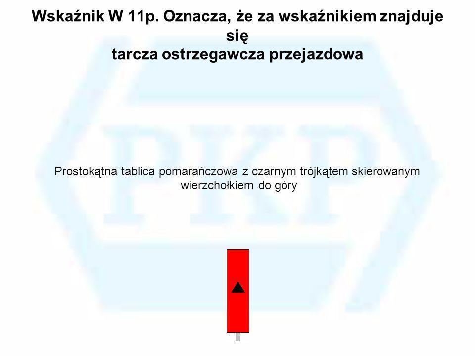Wskaźnik W 11p. Oznacza, że za wskaźnikiem znajduje się tarcza ostrzegawcza przejazdowa Prostokątna tablica pomarańczowa z czarnym trójkątem skierowan