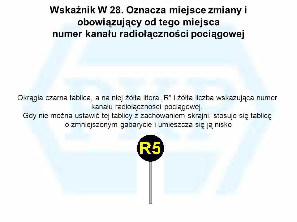 Wskaźnik W 28. Oznacza miejsce zmiany i obowiązujący od tego miejsca numer kanału radiołączności pociągowej Okrągła czarna tablica, a na niej żółta li