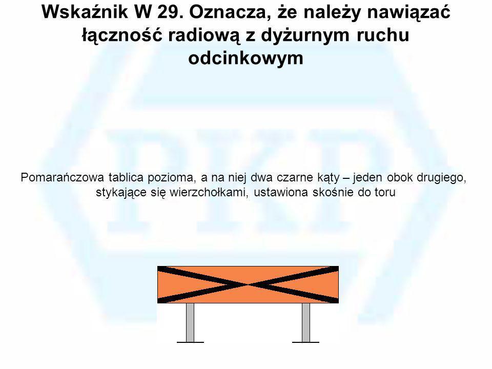 Wskaźnik W 29. Oznacza, że należy nawiązać łączność radiową z dyżurnym ruchu odcinkowym Pomarańczowa tablica pozioma, a na niej dwa czarne kąty – jede