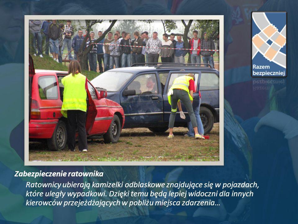Zabezpieczenie ratownika Ratownicy ubierają kamizelki odblaskowe znajdujące się w pojazdach, które uległy wypadkowi.