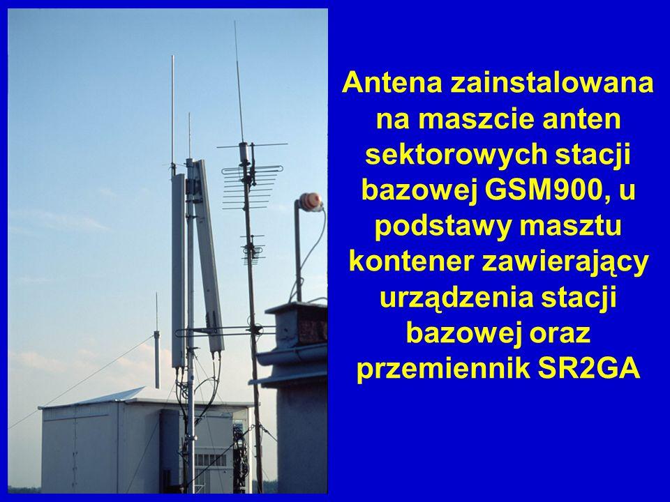 Antena zainstalowana na maszcie anten sektorowych stacji bazowej GSM900, u podstawy masztu kontener zawierający urządzenia stacji bazowej oraz przemie