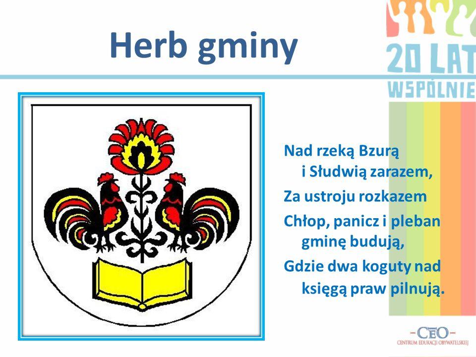 Herb gminy Nad rzeką Bzurą i Słudwią zarazem, Za ustroju rozkazem Chłop, panicz i pleban gminę budują, Gdzie dwa koguty nad księgą praw pilnują.