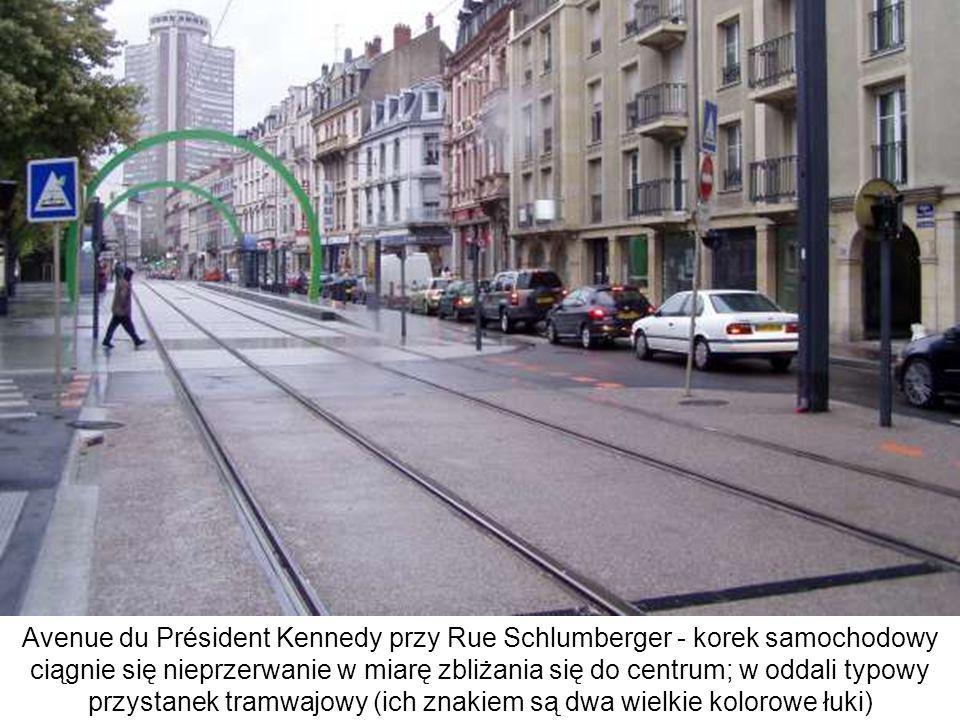 Avenue du Président Kennedy przy Rue Schlumberger - korek samochodowy ciągnie się nieprzerwanie w miarę zbliżania się do centrum; w oddali typowy przy