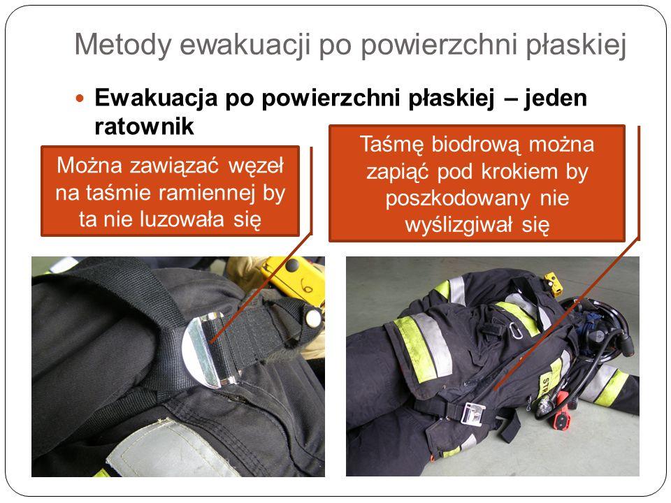 Metody ewakuacji po powierzchni płaskiej Ewakuacja po powierzchni płaskiej – jeden ratownik Można zawiązać węzeł na taśmie ramiennej by ta nie luzował