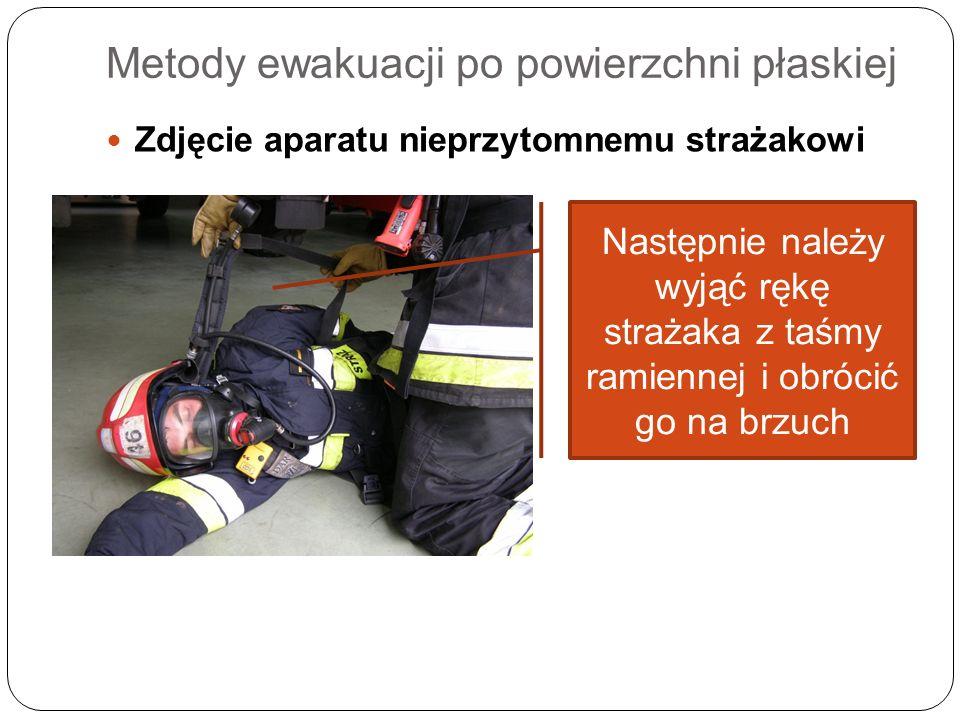 Metody ewakuacji po powierzchni płaskiej Zdjęcie aparatu nieprzytomnemu strażakowi Następnie należy wyjąć rękę strażaka z taśmy ramiennej i obrócić go
