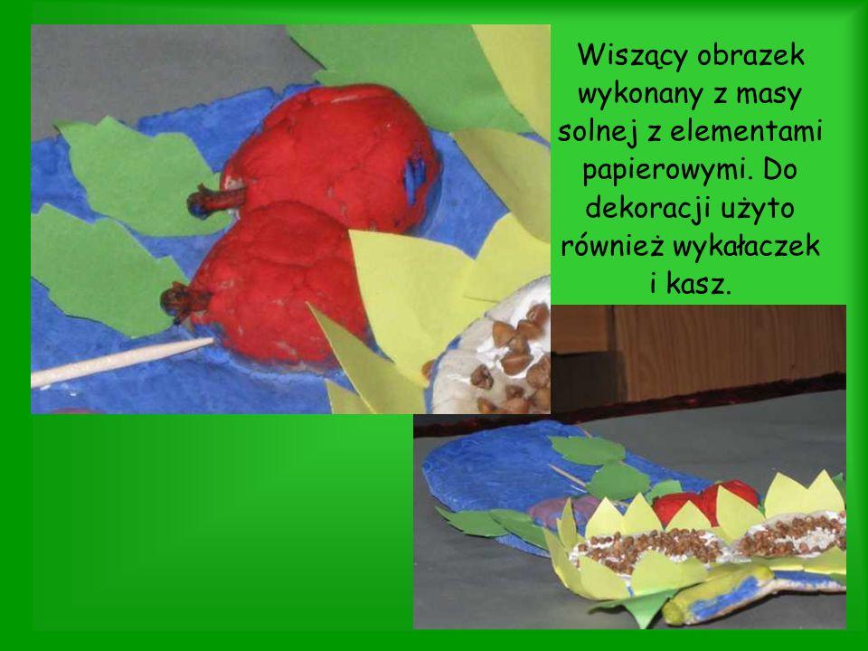 Wiszący obrazek wykonany z masy solnej z elementami papierowymi. Do dekoracji użyto również wykałaczek i kasz.