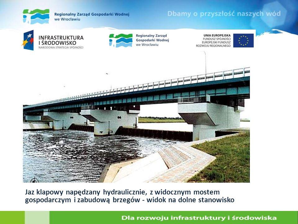 Jaz klapowy napędzany hydraulicznie, z widocznym mostem gospodarczym i zabudową brzegów - widok na dolne stanowisko