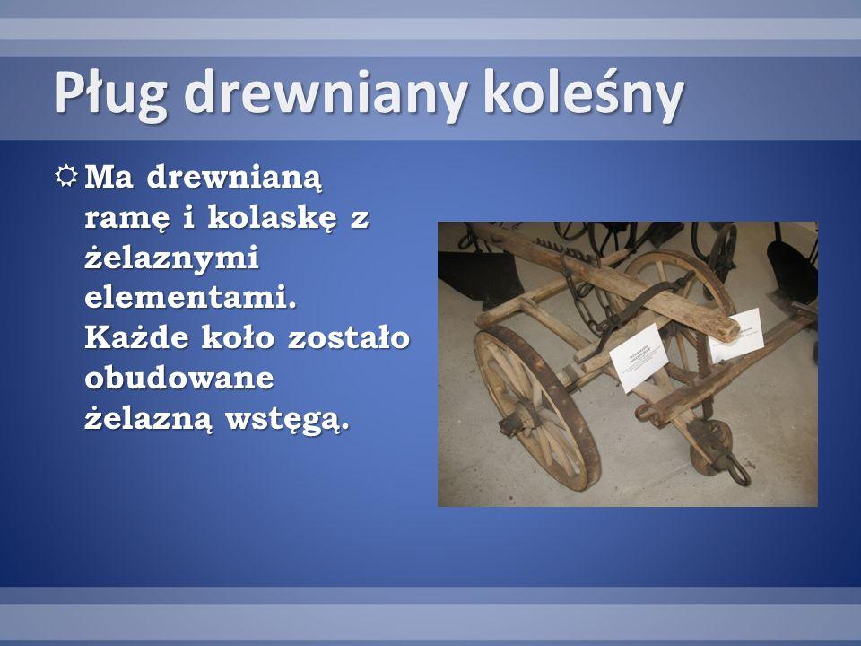 Pług drewniany koleśny Ma drewnianą ramę i kolaskę z żelaznymi elementami.