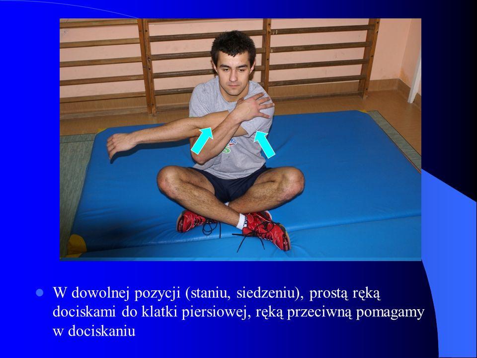 W dowolnej pozycji (staniu, siedzeniu), prostą ręką dociskami do klatki piersiowej, ręką przeciwną pomagamy w dociskaniu