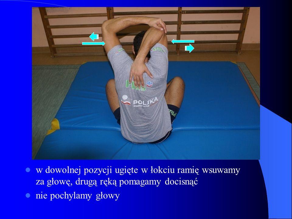 w dowolnej pozycji ugięte w łokciu ramię wsuwamy za głowę, drugą ręką pomagamy docisnąć nie pochylamy głowy