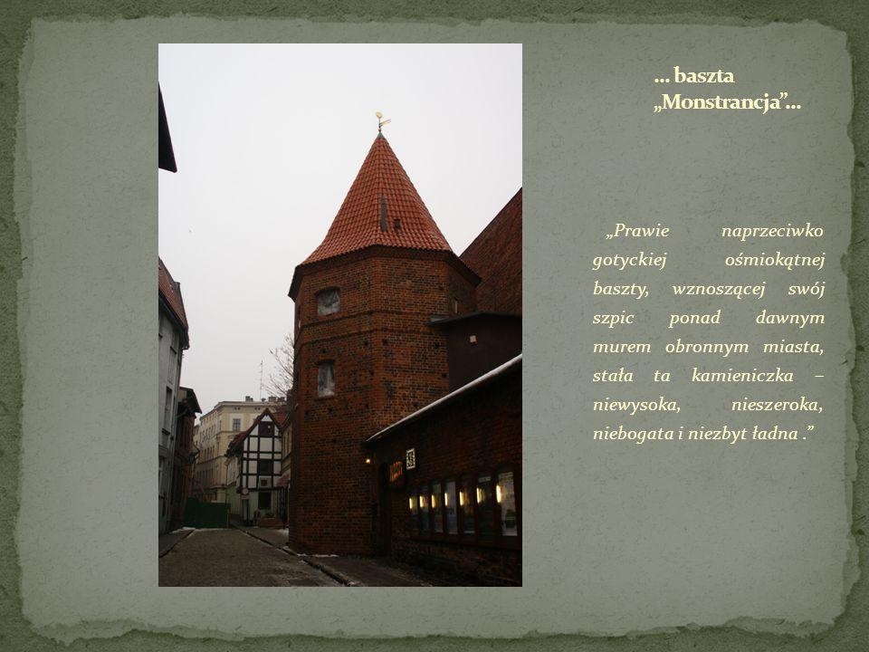 Prawie naprzeciwko gotyckiej ośmiokątnej baszty, wznoszącej swój szpic ponad dawnym murem obronnym miasta, stała ta kamieniczka – niewysoka, nieszerok