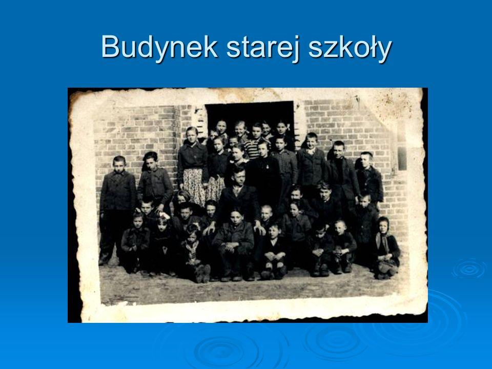 Uczniowie i nauczyciele przed budynkiem szkolnym koło kościoła