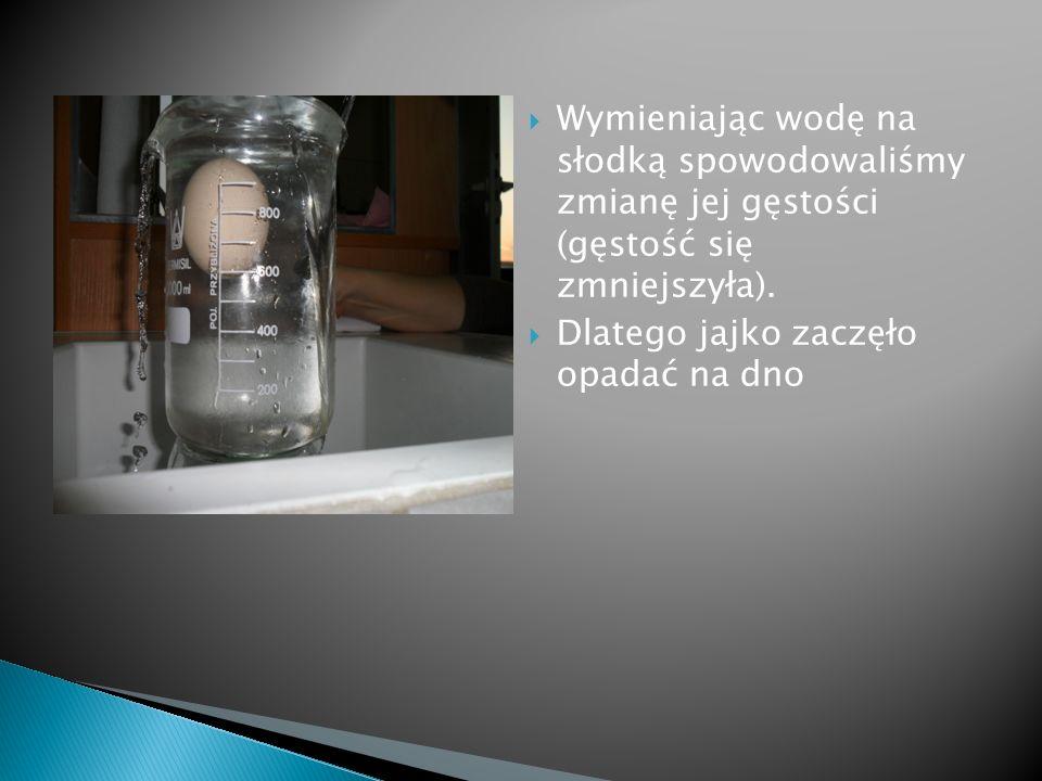 Wymieniając wodę na słodką spowodowaliśmy zmianę jej gęstości (gęstość się zmniejszyła). Dlatego jajko zaczęło opadać na dno