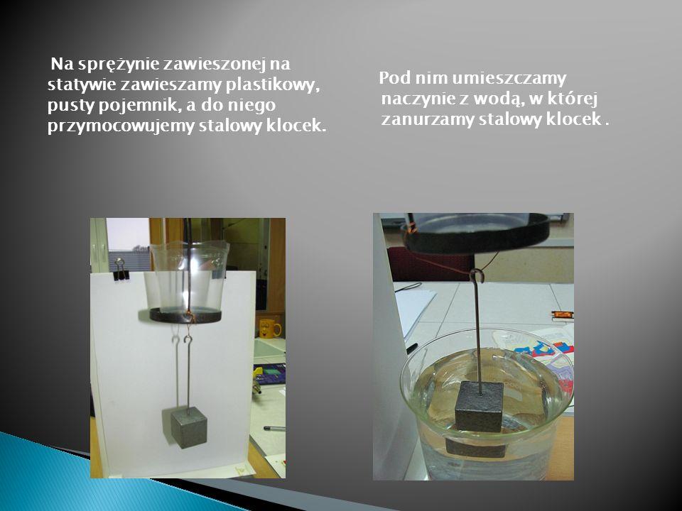 Na sprężynie zawieszonej na statywie zawieszamy plastikowy, pusty pojemnik, a do niego przymocowujemy stalowy klocek. Pod nim umieszczamy naczynie z w