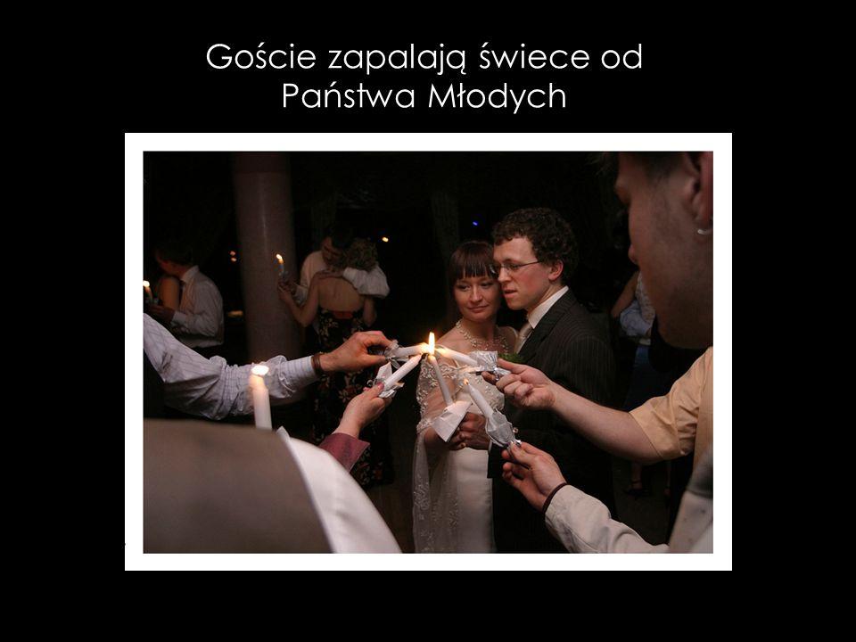 Goście zapalają świece od Państwa Młodych