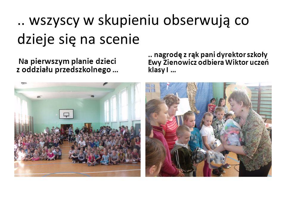 .. wszyscy w skupieniu obserwują co dzieje się na scenie Na pierwszym planie dzieci z oddziału przedszkolnego ….. nagrodę z rąk pani dyrektor szkoły E