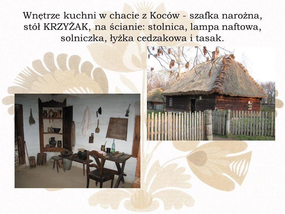 Wnętrze kuchni w chacie z Koców - szafka narożna, stół KRZYŻAK, na ścianie: stolnica, lampa naftowa, solniczka, łyżka cedzakowa i tasak.