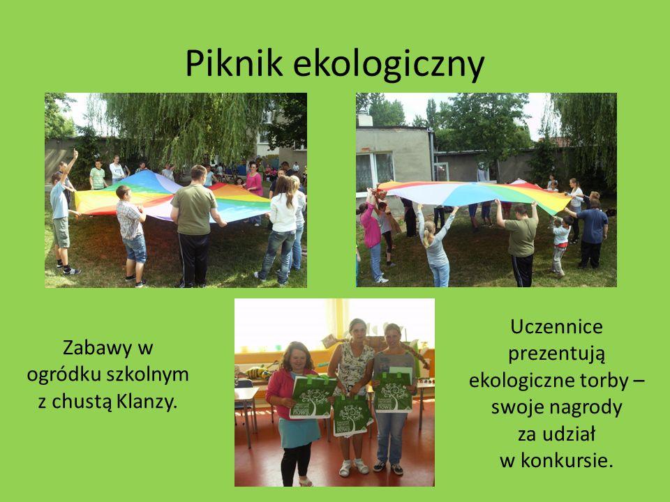 Piknik ekologiczny Zabawy w ogródku szkolnym z chustą Klanzy. Uczennice prezentują ekologiczne torby – swoje nagrody za udział w konkursie.
