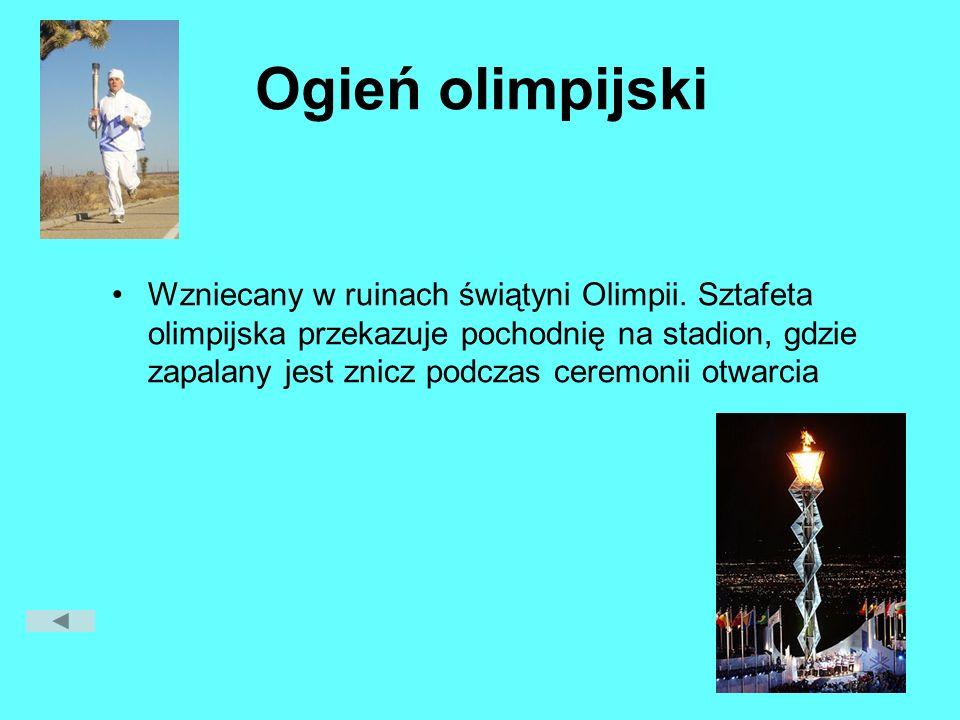 Ogień olimpijski Wzniecany w ruinach świątyni Olimpii. Sztafeta olimpijska przekazuje pochodnię na stadion, gdzie zapalany jest znicz podczas ceremoni
