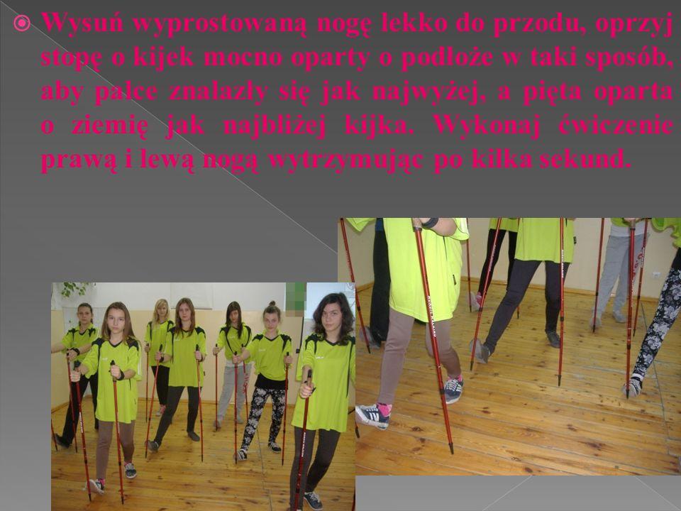Wysuń wyprostowaną nogę lekko do przodu, oprzyj stopę o kijek mocno oparty o podłoże w taki sposób, aby palce znalazły się jak najwyżej, a pięta opart