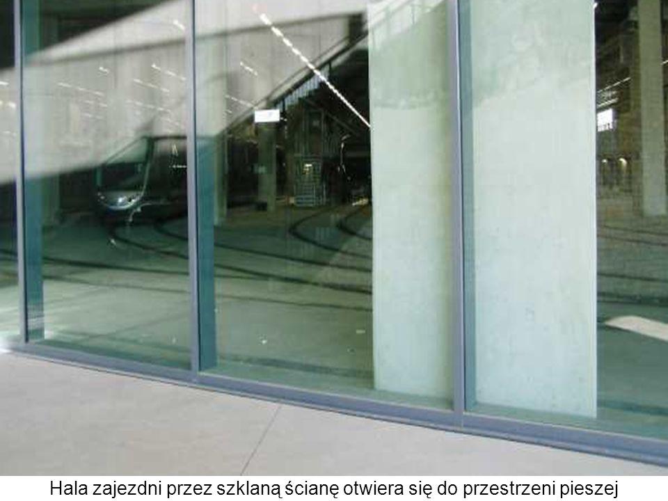 Hala zajezdni przez szklaną ścianę otwiera się do przestrzeni pieszej