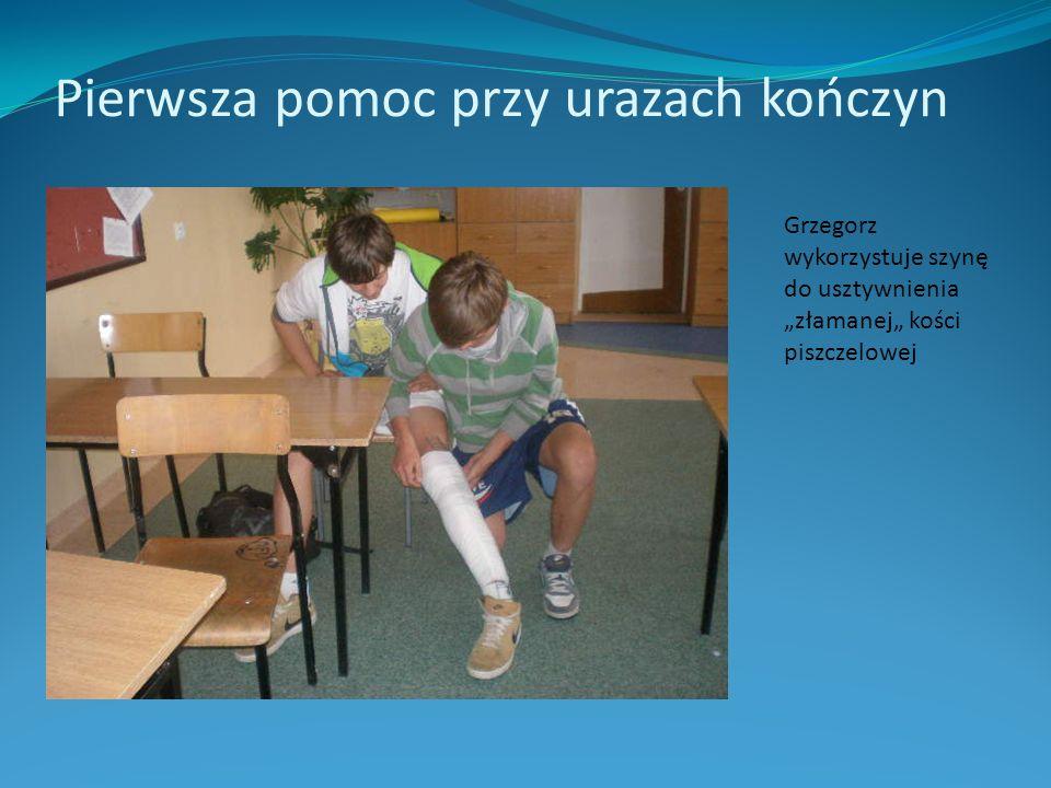 Pierwsza pomoc przy urazach kończyn Grzegorz wykorzystuje szynę do usztywnienia złamanej kości piszczelowej