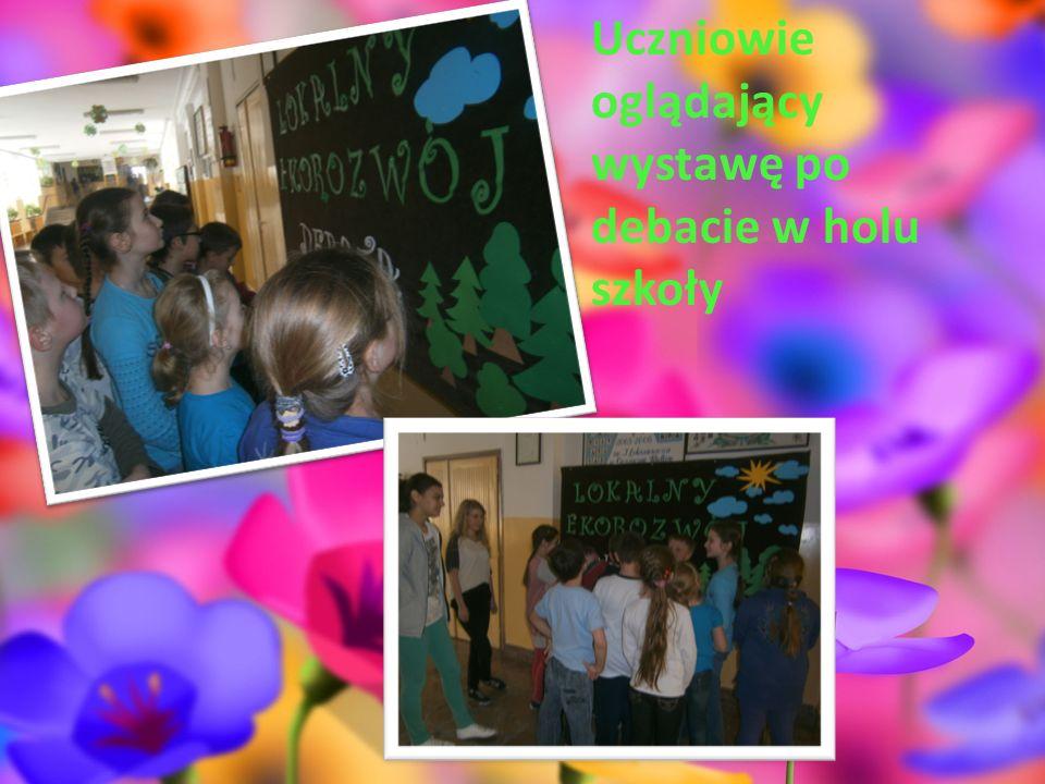 Uczniowie oglądający wystawę po debacie w holu szkoły