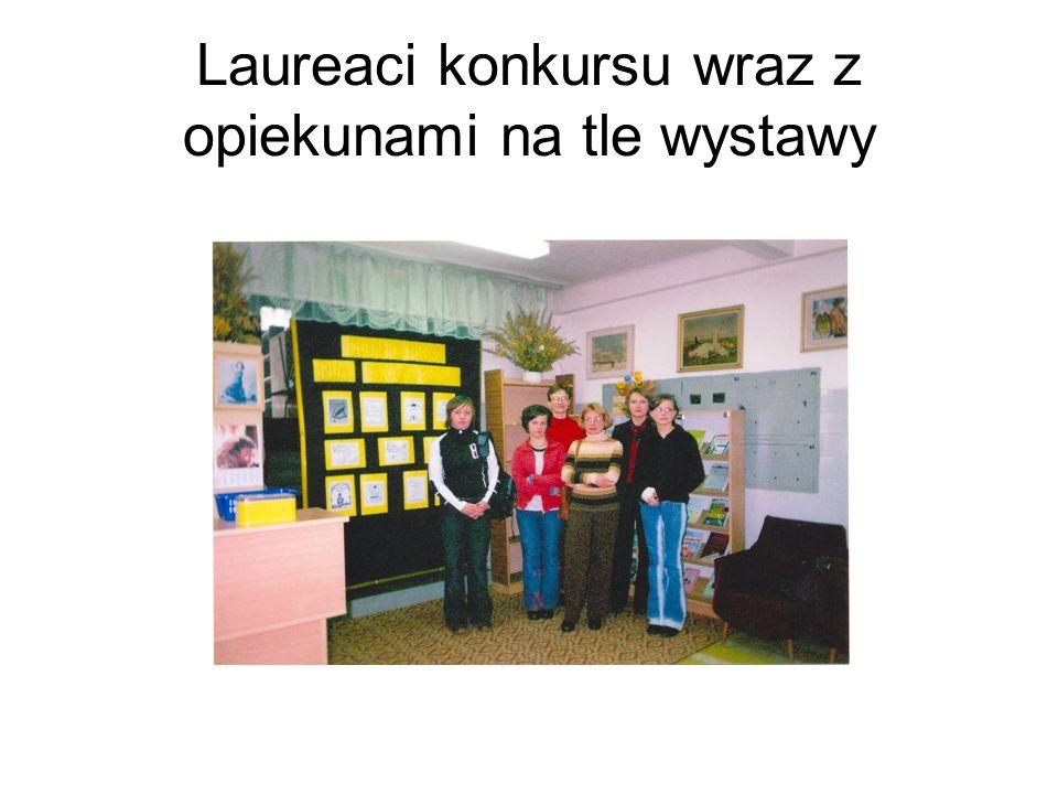 Laureaci konkursu wraz z opiekunami na tle wystawy