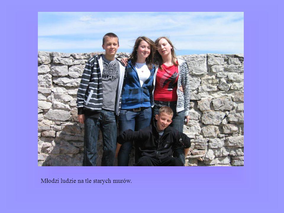 Młodzi ludzie na tle starych murów.