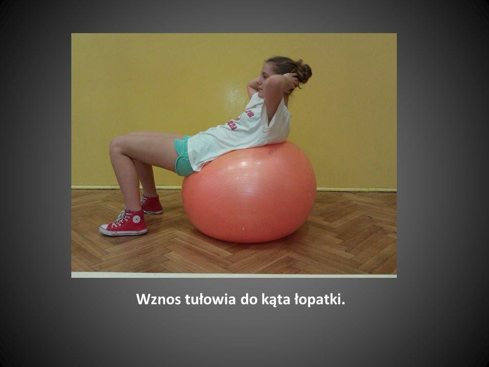 Obydwa kolana i podudzia na piłce.Ręce proste oparte na podłodze na szer.