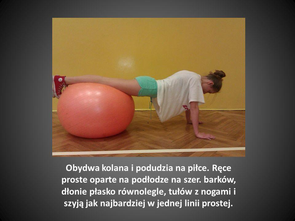Przyciągamy piłkę do siebie wypychając biodra do góry, a kolana do klatki piersiowej.