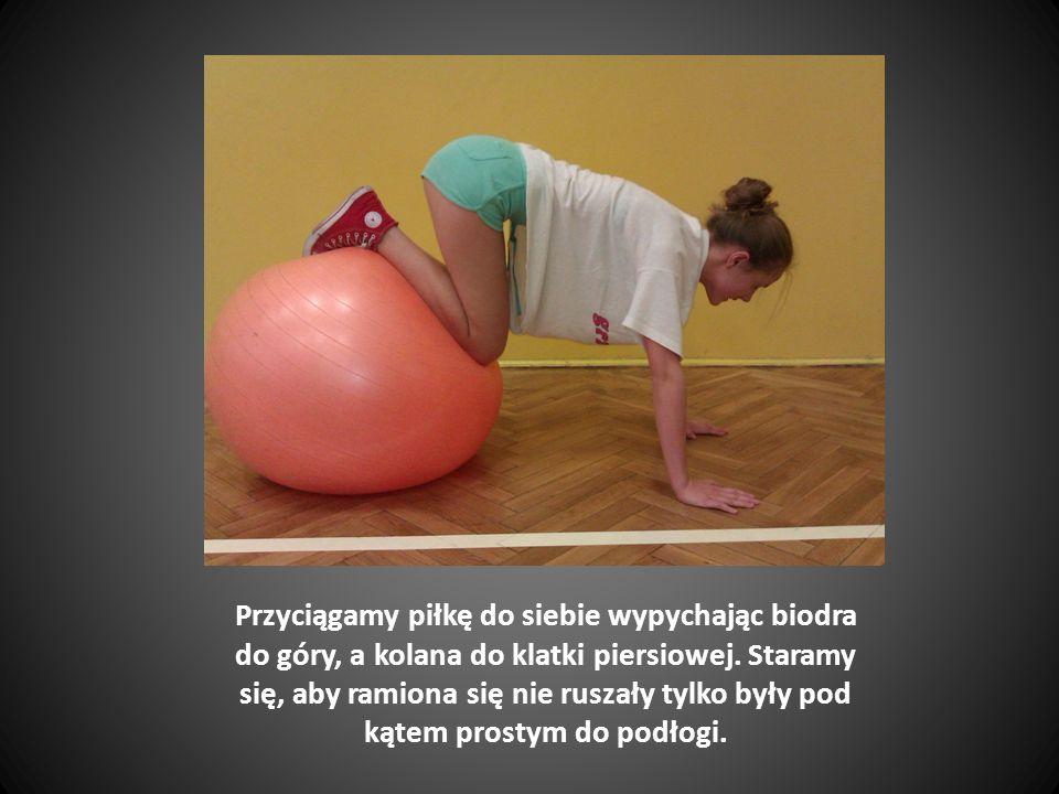 Piłkę opieramy o ścianę w okolicy łopatek, stopy na szerokość bioder, kolana nie powinny wychodzić przed kostki.