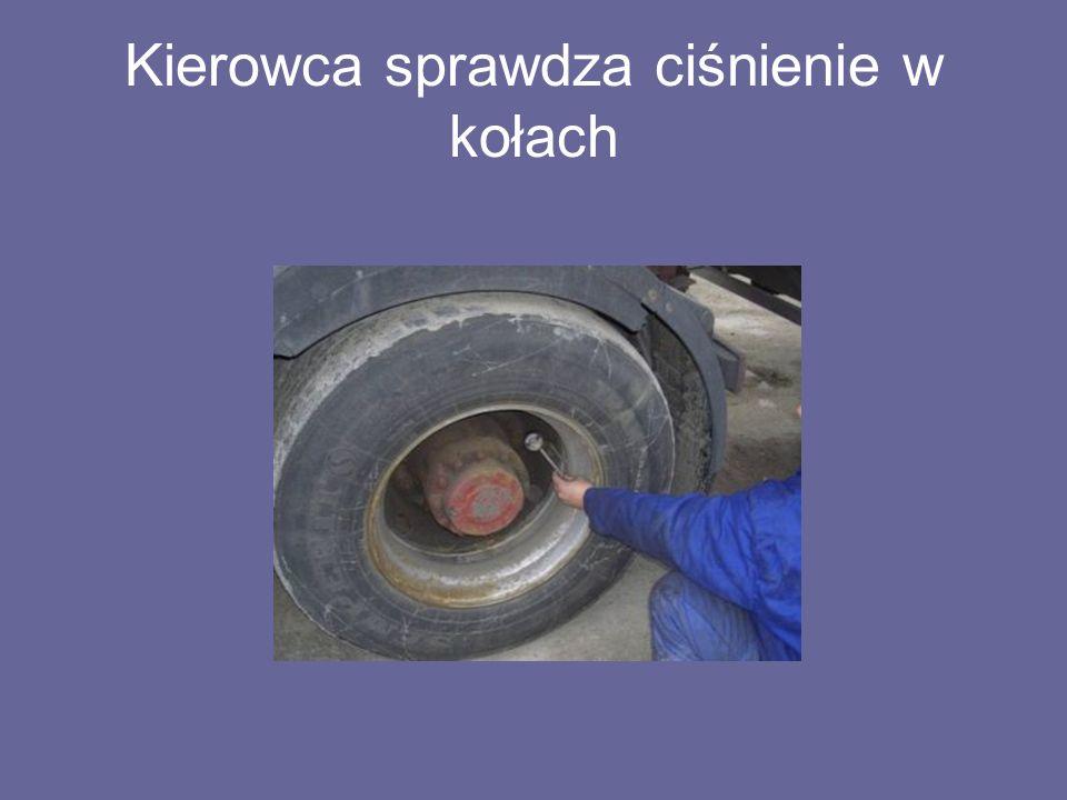 Kierowca sprawdza ciśnienie w kołach