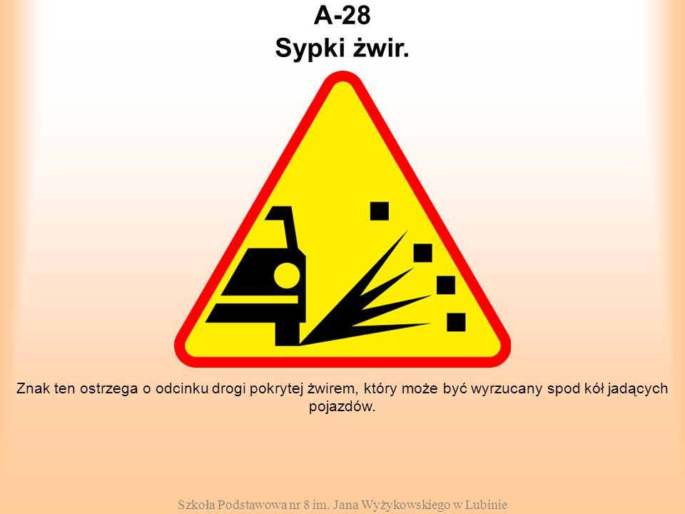Szkoła Podstawowa nr 8 im. Jana Wyżykowskiego w Lubinie A-28 Znak ten ostrzega o odcinku drogi pokrytej żwirem, który może być wyrzucany spod kół jadą
