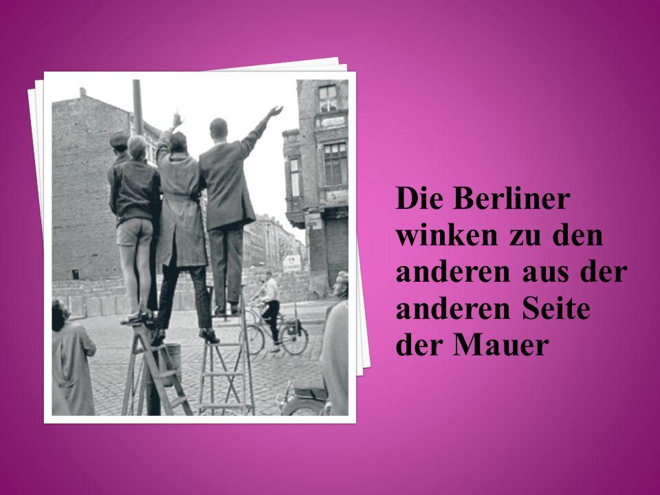 Die Berliner winken zu den anderen aus der anderen Seite der Mauer