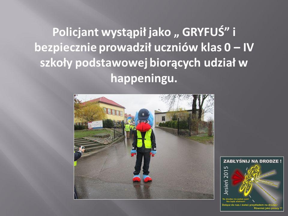 """Policjant wystąpił jako """" GRYFUŚ i bezpiecznie prowadził uczniów klas 0 – IV szkoły podstawowej biorących udział w happeningu."""