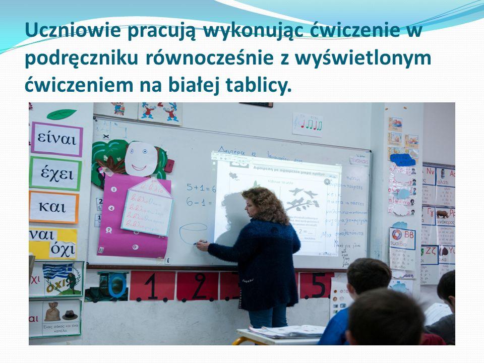 Uczniowie pracują wykonując ćwiczenie w podręczniku równocześnie z wyświetlonym ćwiczeniem na białej tablicy.