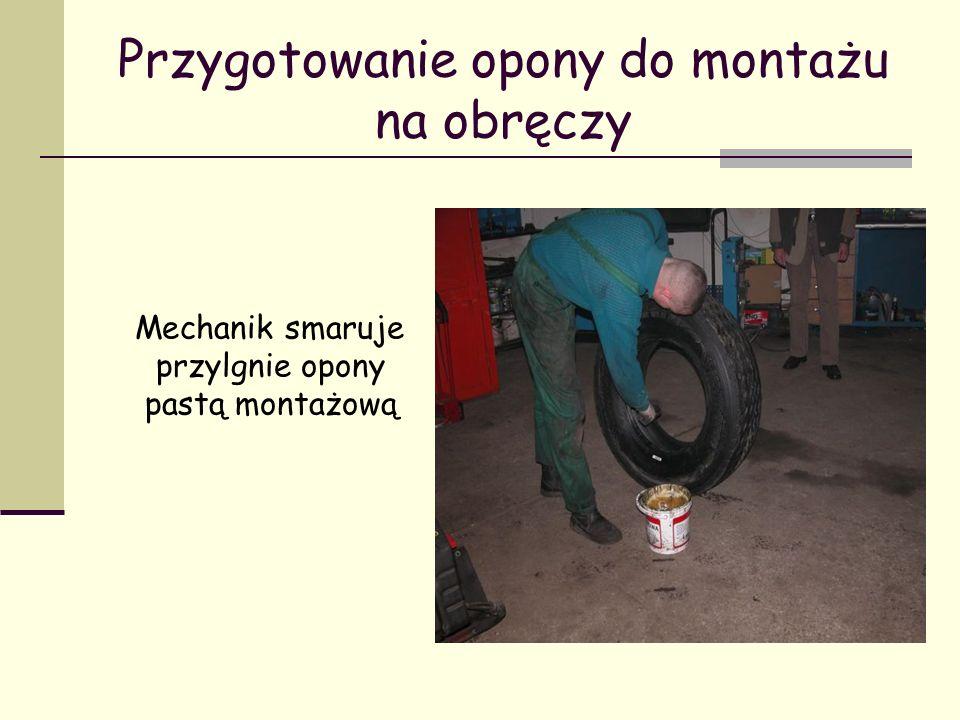 Przygotowanie opony do montażu na obręczy Mechanik smaruje przylgnie opony pastą montażową