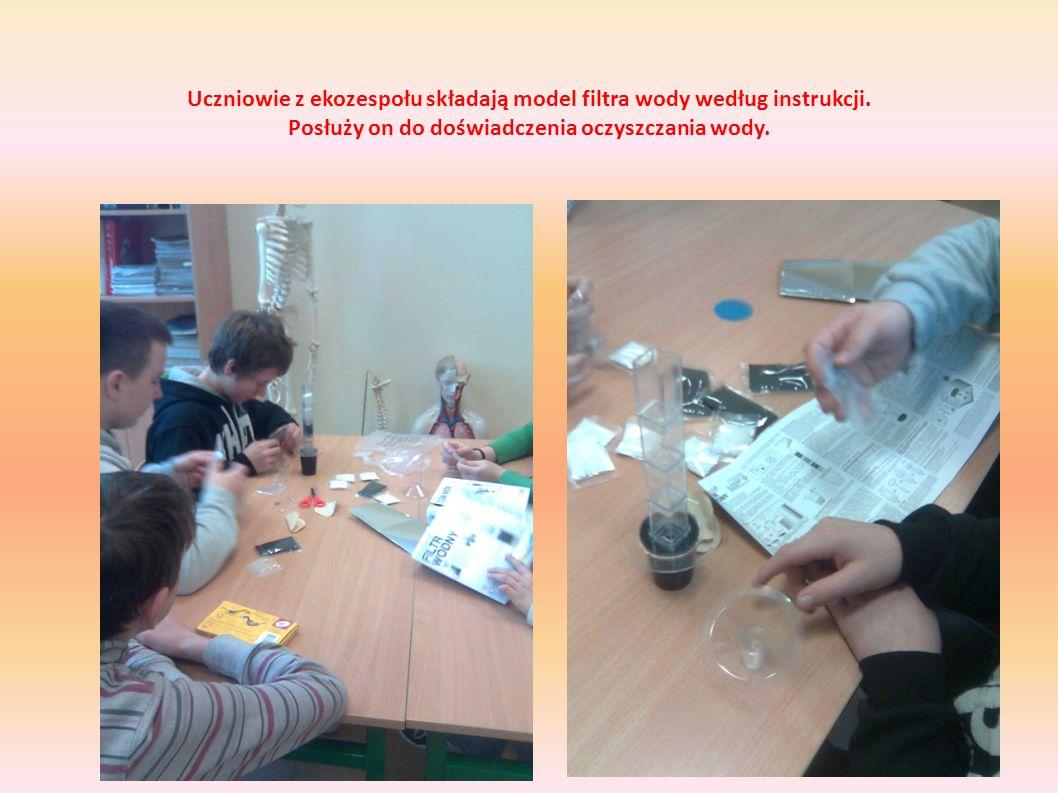 Uczniowie z ekozespołu składają model filtra wody według instrukcji. Posłuży on do doświadczenia oczyszczania wody.