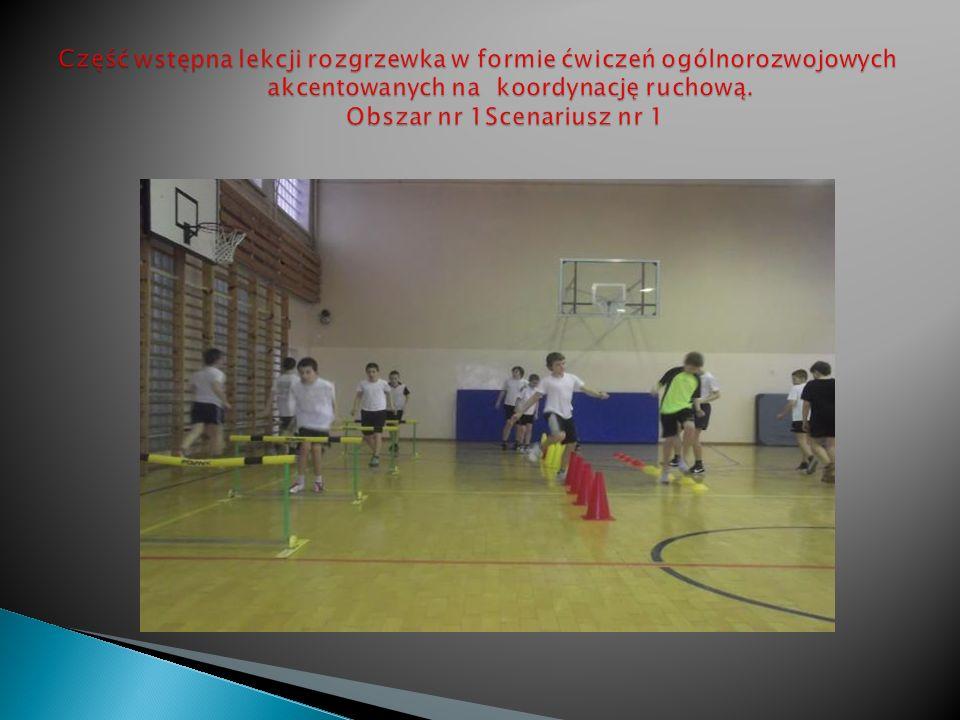 Rywalizacja, na trasie biegu przełajowego widoczne przeszkody dostosowane w każdym biegu do możliwości i wieku ćwiczących