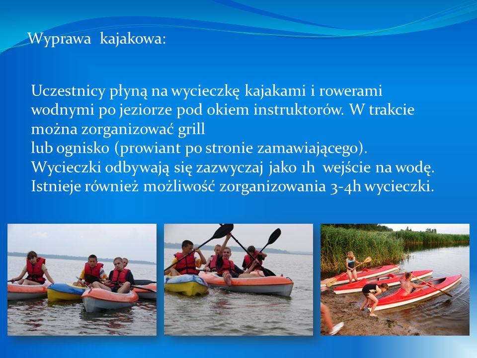 Uczestnicy płyną na wycieczkę kajakami i rowerami wodnymi po jeziorze pod okiem instruktorów.