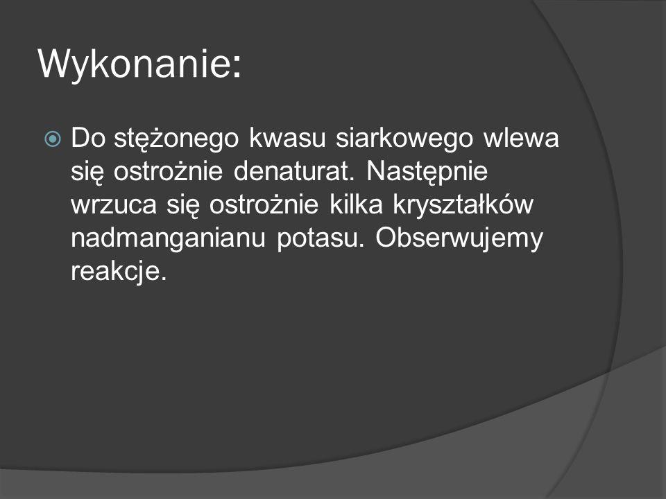 Wykonanie: Do stężonego kwasu siarkowego wlewa się ostrożnie denaturat. Następnie wrzuca się ostrożnie kilka kryształków nadmanganianu potasu. Obserwu