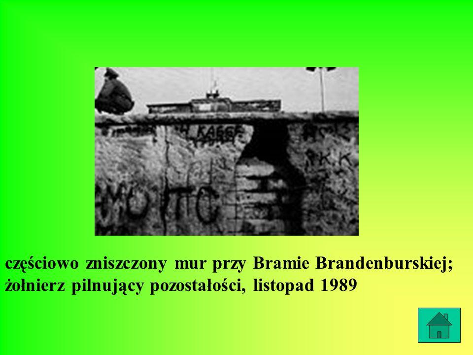 częściowo zniszczony mur przy Bramie Brandenburskiej; żołnierz pilnujący pozostałości, listopad 1989