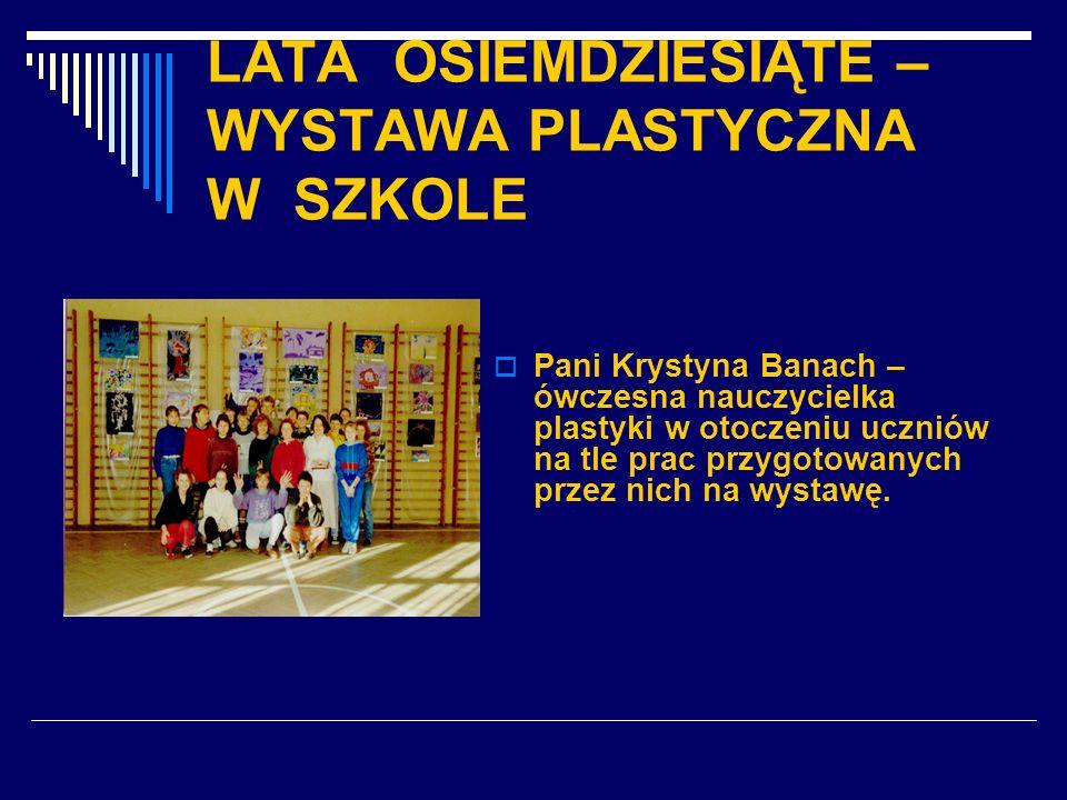 LATA OSIEMDZIESIĄTE – WYSTAWA PLASTYCZNA W SZKOLE Pani Krystyna Banach – ówczesna nauczycielka plastyki w otoczeniu uczniów na tle prac przygotowanych
