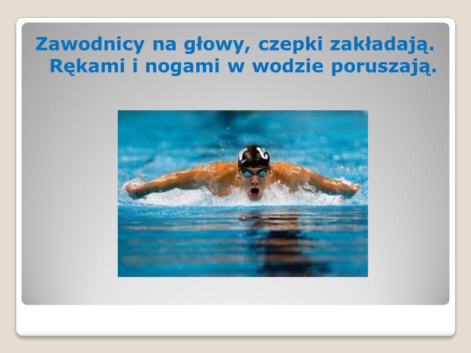 Zawodnicy na głowy, czepki zakładają. Rękami i nogami w wodzie poruszają.