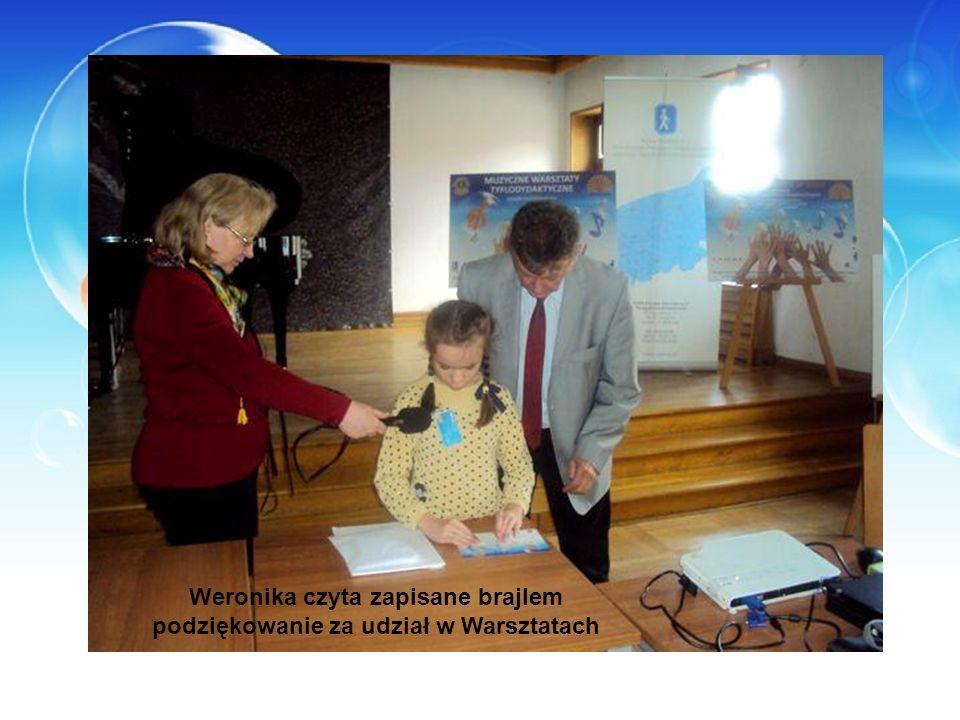 Weronika czyta zapisane brajlem podziękowanie za udział w Warsztatach